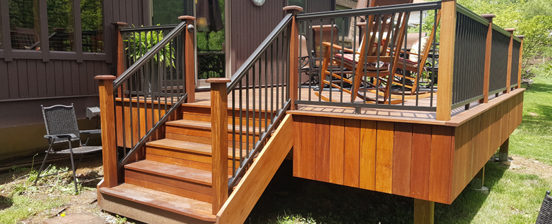 A beautiful back yard deck with stairs leading up to a house.