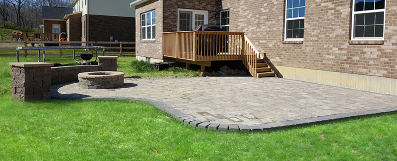 An image of a backyard with a paver patio, fire put and seating walls done by Outdoor Envy.