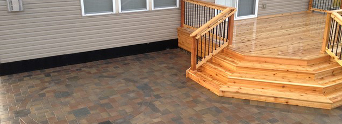 A paver patio and deck combination looking great in a backyard.